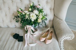 Wedding bouquet, pink bridal shoes and black boxes with rings on a luxury sofa. Indoors. Artwork