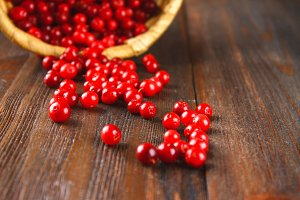 Cowberry, foxberry, cranberry, lingonberry sips from the basket on a brown wooden table.