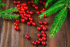 Cowberry, foxberry, cranberry, lingonberry sips on a brown wooden table. Surrounded by fir branches.