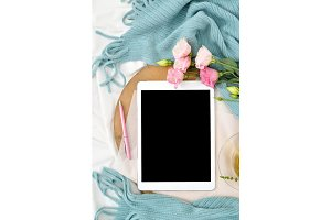 Vertical Flat lay tablet and flowers on white blanket with turquoise plaid