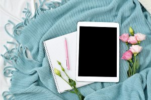 Flat lay tablet, phone, cup of coffee and flowers on white blanket with turquoise plaid