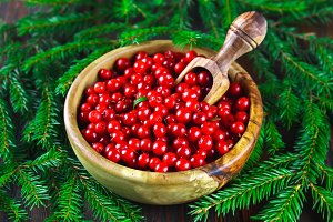 Cowberry, foxberry, cranberry, lingonberry in a wooden bowl with a scoop on a brown wooden table. Surrounded by fir branches.