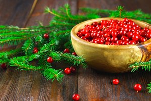 Cowberry, foxberry, cranberry, lingonberry in a wooden bowl on a brown wooden table. Surrounded by fir branches.