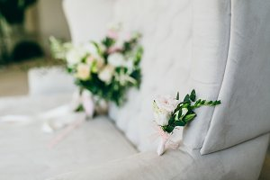 Groom's boutonniere of flowers and greens lies on the luxury sofa. Artwork