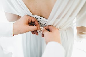 Groom helps fasten a wedding dress the bride before the ceremony. Wedding concept. Close-up Artwork
