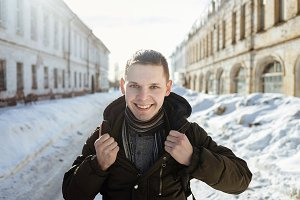 A happy smiling man wearing a fur trendy warm scarf posing in the city.