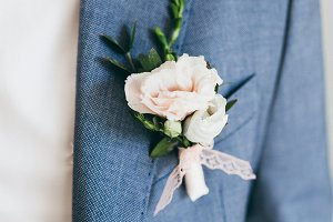 Close up image of beautiful boutonniere on the groom's jacket. Soft focus on boutonniere. Artwork