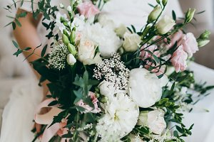 Gorgeous bouquet of white and pink flowers in the hands of the charming bride in a white dress. Artwork
