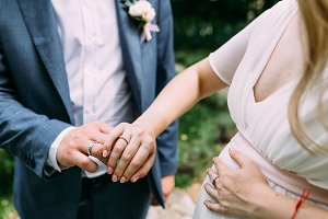 Bride and groom showing wedding rings. Artwork. Soft focus