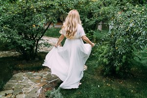 Gorgeous blonde bride in white dress is walking in the green garden. Back view. Artwork.