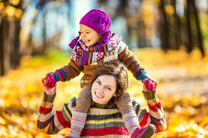 Mother and daughter playing in autumn park