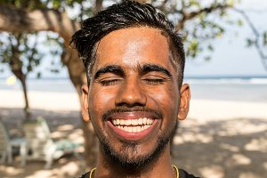 Close up portrait of young smiling asian indian yoga man outside. Park, beachside. Bali island.