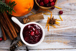 Cranberry sauce with ingredients on wooden table