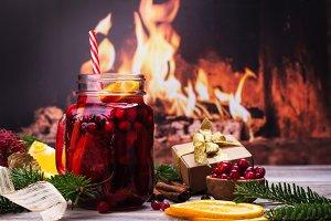 Cranberry and orange winter sangria near fireplace