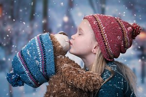 A little girl kisses a Teddy bear. snowing, winter