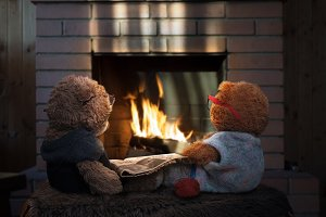 Two toy bear by the fireplace with a newspaper and knitting. The concept of toys as people - an old grandmother and grandfather together.Old age, caring for parents, love of family