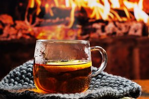 Hot tea with lemon, old vintage book near fireplace