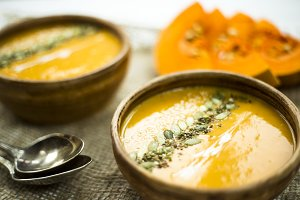 pumpkin soup in a clay dish decorated with pumpkin seeds, sesame seeds, spices and cream