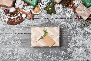 Gift boxes, Christmas decorations and pine cones on gray wooden table. Christmas background. Space for text. Top view.