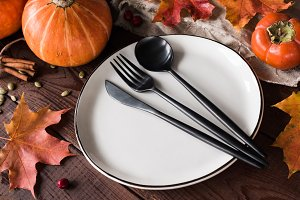 Thanksgiving table setting with pumpkins, wheat, fallen leaf and black cutlery
