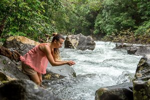 the girl drinks water from a mountain stream