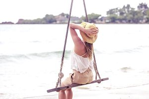 girl on a swing on the beach of Thailand