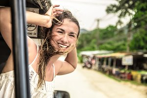 smiling girl looks out of the window of a taxi