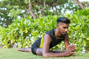 Young yoga man practitioners doing yoga on nature. Asian indian yogis man on the grass in the park. Bali island.