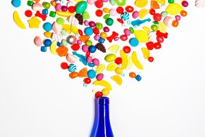 Blue bottle with colorful candy explosion