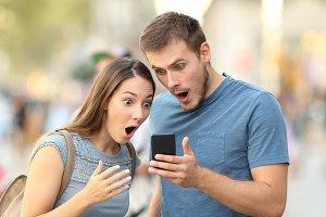 Amazed couple watching on line