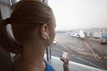 Woman in headphones looking at aipor