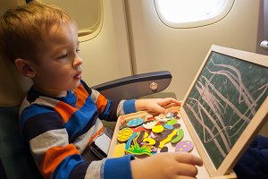 Boy in the plane drawing on board wi
