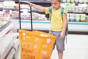 Little boy with big shopping cart in