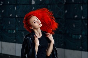 Expressive Redhead woman posing at dark wall and her hair flying against black background