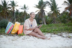 Woman relaxing with pad on beach aft