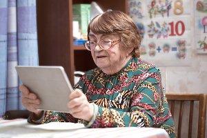 Elderly woman in glasses watching so