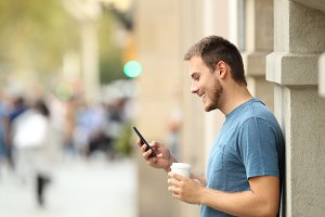 Side view of a happy man using phone