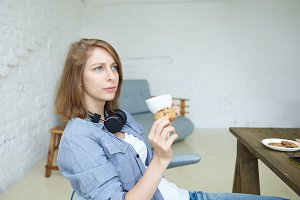 Side view portrait of beautiful young woman dressed casually eating cookie and drinking cappuccino or tea during coffee break while working in modern office interior, sitting at wooden table