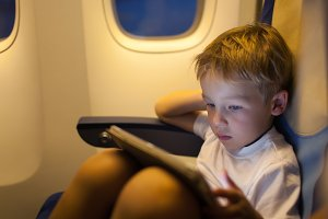 Boy sitting in the plane and using t