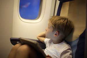 Boy in plane looking out illuminator