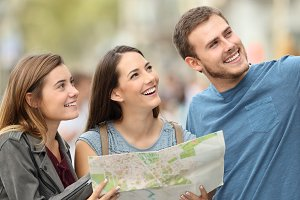 Three happy tourists holding a map