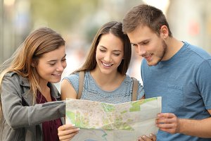 Three happy tourists consulting map