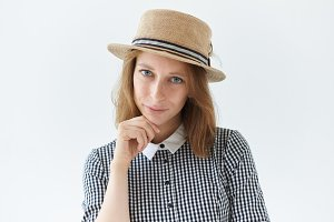 Portrait of romantic young Caucasian female with pure freckled skin wearing retro round hat and checkered collar dress holding hand on her chin looking at camera with pensive dreamy mysterious smile