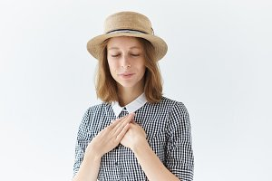 Grateful young woman in round hat holding both hands on chest and closing eyes, expressing gratitude and appreciation. Friendly sincere joyful girl saying thanks, her heart is full with love