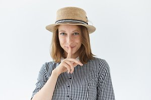 Studio shot of enigmatic beautiful romantic young freckled lady wearing collar dress and retro hat smiling mysteriously, holding finger at her lips, asking to keep something a secret. Body language