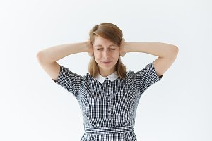 Stop making this annoying sound! Portrait of angry frustrated young woman with headache or migraine covering ears with hands and keeping eyes closed, feeling stressed, can't stand irritating noise