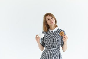Isolated studio shot of pretty girl in elegant collar dress drinking tea holding white mug and oatmeal cookie. Happy young female enjoying coffee with biscuit, smiling with pleasure and enjoyment