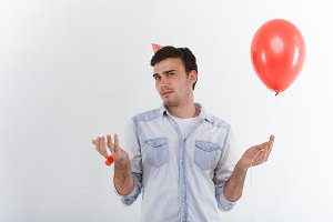 Confused unshaven birthday guy wearing stylish denim shirt and holiday cap looking at camera with clueless puzzled expression, standing in studio with party horn and red balloon in his hands