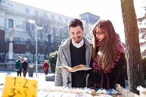 young couple looking at book in the street