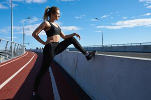 Outdoor summer sideways shot of confident blonde young woman with ponytail wearing black sneakers, top and leggings stretching along pathway before run. Fit athletic girl exercising in the morning